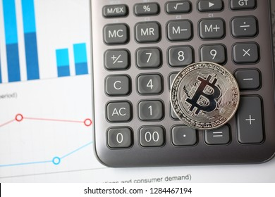 Silver btc sign coin lying at stats graph closeup. Modern pay and buy system symbol idea virtual earning and anti fraud transactions broker consultant education and career success ambition concept