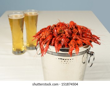 silver bucket of boiled crawfish served with beer