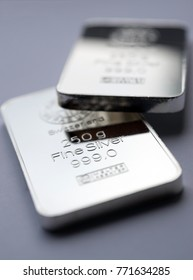 Silver bullion bars. Two fine silver bars on a grey background. Selective focus.