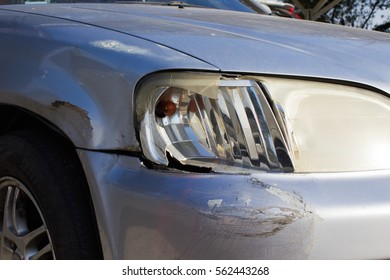 Silver bumper car scratched with deep damage to the paint and crushed with front light of car broken