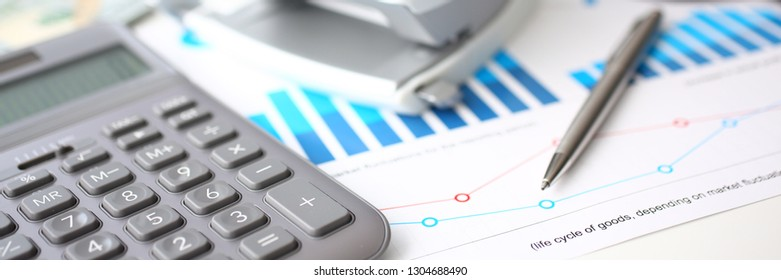 Silver calculator and financial statistics on clipboard pad at office table closeup. Internal Revenue Service inspector sum check irs investigation earnings savings loan and credit concept