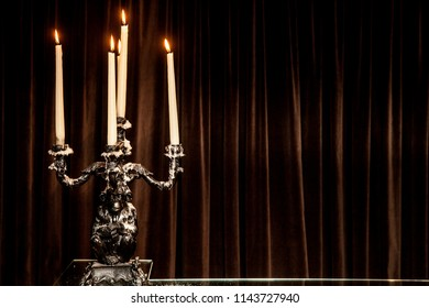 silver candle holder with candles lit on a table. brown background
