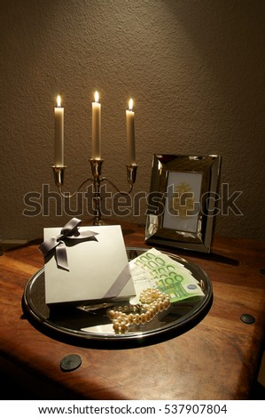 Silver Candle Holder Picture Frame And Banknotes On Tray Decorated Wooden Table