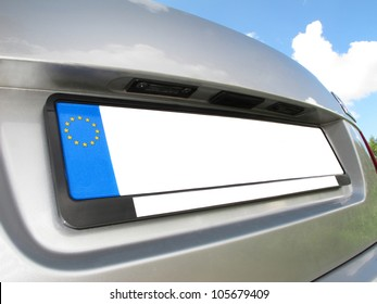 Silver car back view with empty white  number plate on  blue sky with clouds background