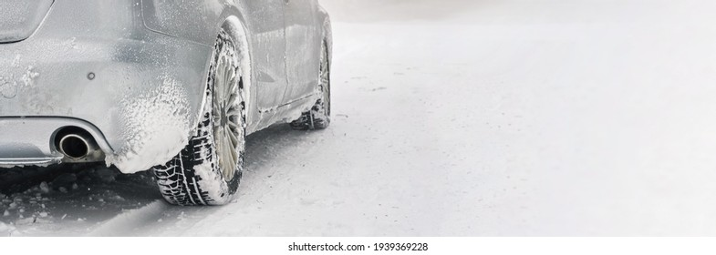 Silver car covered with ice parked on snow covered road, detail view to exhaust from behind, background empty space for text right side