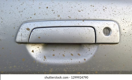 Silver car door handle close up, visible drops of dirt