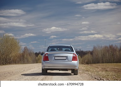 Silver car on a gravel road against a blue sky with clouds. Back view. Car journey.