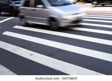 Silver car passing over crosswalk, it's daylight and motion is blurred.