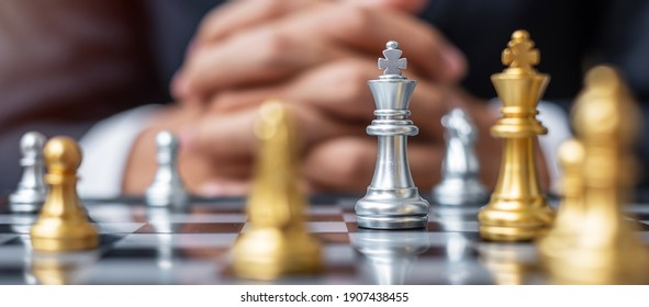 silver Chess King figure against goal chessboard opponent with businessman manager background. Strategy, Success, management, business planning, tactic, politic, thinking,vision and leadership concept