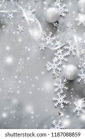 Silver Christmas background. Curly ribbon with decorative balls and snowflakes. Xmas decorations. Copy space, snow effect.
