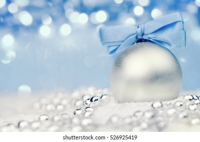 Silver Christmas ball on shiny background with blue ribbon