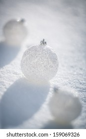 Silver Christmas balls on real snow outdoors. Winter holidays concept. Shallow depth of fields