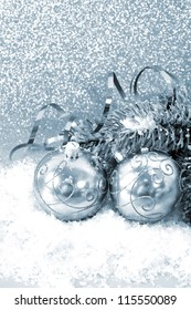 silver christmas balls with christmas tree branch in snow