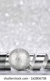 Silver Christmas decoration ball and ribbon on glitter background