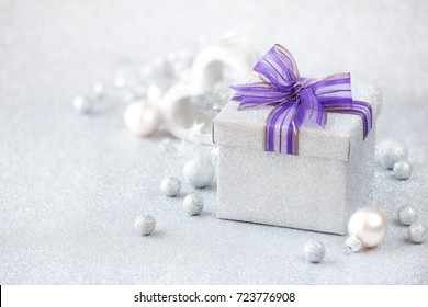 Silver Christmas setting - beautiful glitter silver gift box with a purple bow with silver baubles and a heart shaped xmas decoration at the background