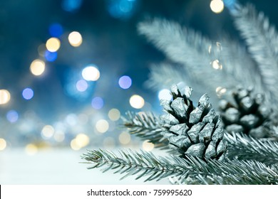 silver christmas tree branch with pine cones on blurred blue background with lights