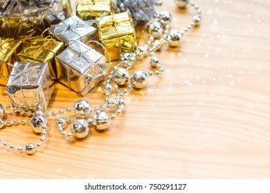 A silver Christmas tree is on the wooden table decorated with gift boxes, pines and snowflake. Wooden table background.