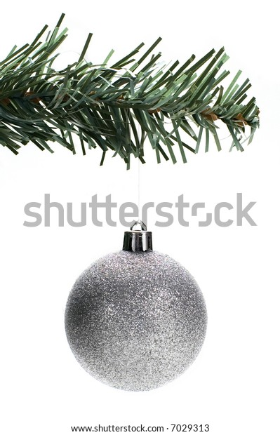 Silver Christmas tree ornament hangs from a pine tree branch on a white background