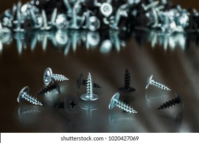 silver chrom and black anodized screws on mirror background
