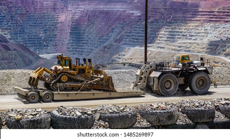Silver City, New Mexico USA - July 30, 2019: Heavy duty towing vehicle pulls a large bulldozer along an access road in the Santa Rita open pit Chino mine to excavate copper ore.