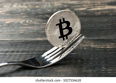 Silver coin bitcoin with a fork on wooden background