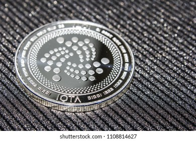 Silver coin cryptocurrency IOTA. MIOTA on grey background.