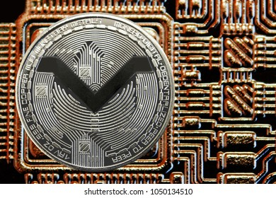 Silver coin cryptocurrency MoneroV on a background of gold circuit.