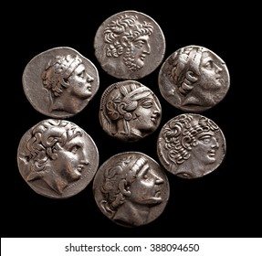 Silver coins of ancient Greece on a black background top view, selective focus