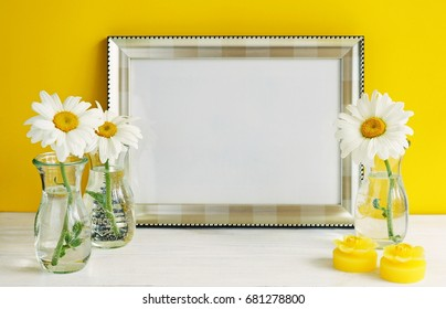 Silver color frame mockup with chamomile flowers in vases on a yellow background. Copy space