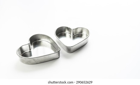 Silver color metal stainless steel heart love shaped pastry baking mould container. Isolated on white background. Concept of tools for lovely cake making. Copy space.