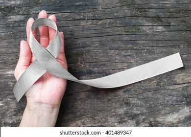 Silver color ribbon awareness on helping hand, aged wood, symbolic bow color for Parkinson's disease, brain cancer, Schizophrenia, Sciatic Pain and brain disorder or disability illness