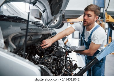 Silver colored laptop in hand. Employee in the blue colored uniform works in the automobile salon.