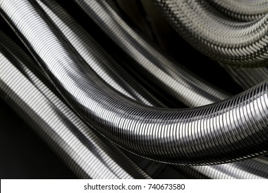 Silver colored metal hoses as grooved tubes. Flexible connector.