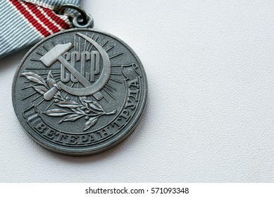 Silver colored Russian veteran war medal with soviet hammer and sickle on a white surface. Copyspace area for military themes and designs.
