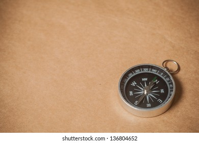 A silver compass with black face pointing north on a brown paper background.