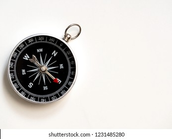 Silver compass pointing west on white background