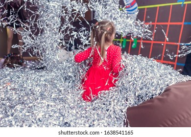 A lot of silver confetti. Girl in a red dress among a falling silver confetti party