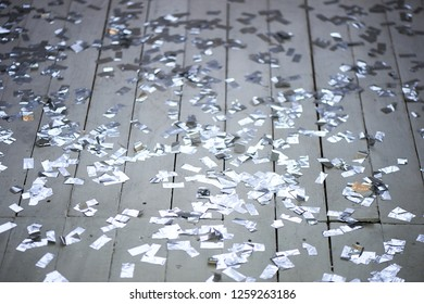 Silver confetti scattered on a white wooden floor. New year party.