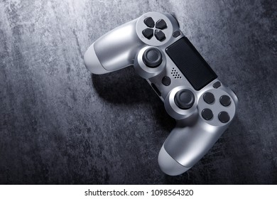 Silver console gamepad, game controller on black texture background