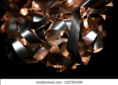 Silver and copper metal curved ribbon chandelier closeup. Modern metal lampshade. Black and white abstract textured  background. Abstract chaotic pattern. Futuristic backdrop. Interior decoration.