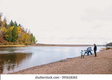 Silver Creek Township, MN, USA - OCTOBER 14, 2015: Gooseberry Falls State Park.Unknown family play ducks and drakes near Lake Superior, Minnesota