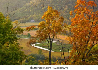 A silver creek winds through a valley pasture below tree-covered hills in Autumn