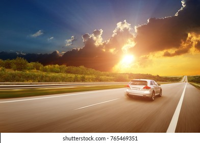 A silver crossover car driving fast on the countryside asphalt road against night sky with clouds and a beautiful sunset