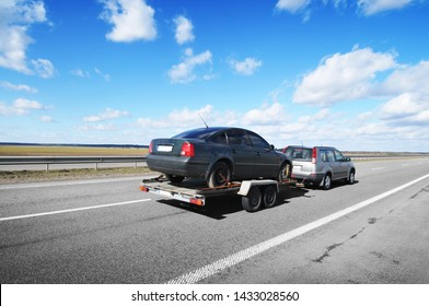 A silver crossover with trailer towing a saloon car on the asphalt countryside road against blue sky with clouds