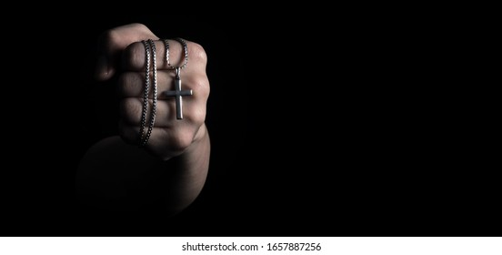Silver crucifix or cross pendant and necklace on body or hand studio shot black color background which represent to praying for god or jesus for christian religion people who have faith