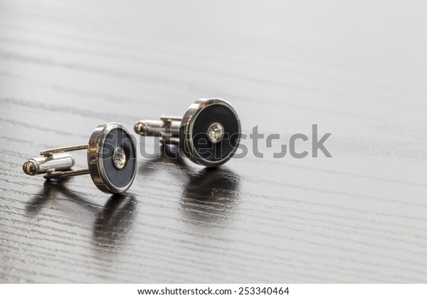 silver cuff links on wooden table colse up