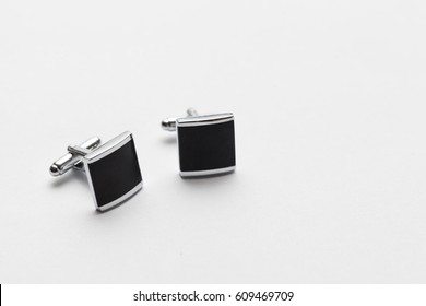 silver cufflinks on white background, close up