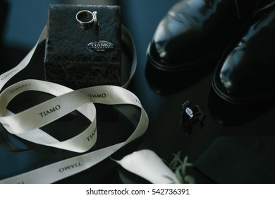 Silver cufflinks, wedding rings and leather shoes stand on glass table