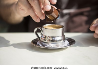 silver cup of coffee with a man's hand pouring cream milk