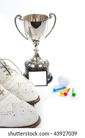 A silver cup  and golf shoes with white space on cup for copy
